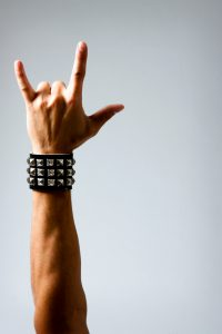 close up of Man with studded wristband making rock symbol. Studio photo with Dramatic lighting, slight vignette for effect.